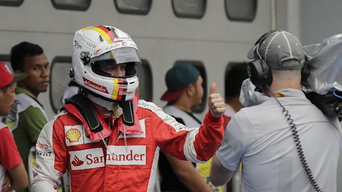 Ferrari driver Sebastian Vettel of Germany shows a thumbs-up after finishing second in the qualifying session for the Malaysian Formula One Grand Prix at Sepang International Circuit in Sepang, Malaysia, Saturday, March 28, 2015. Mercedes driver Lewis Hamilton of Britain took pole position for Sunday's race. (AP Photo/Andy Wong)