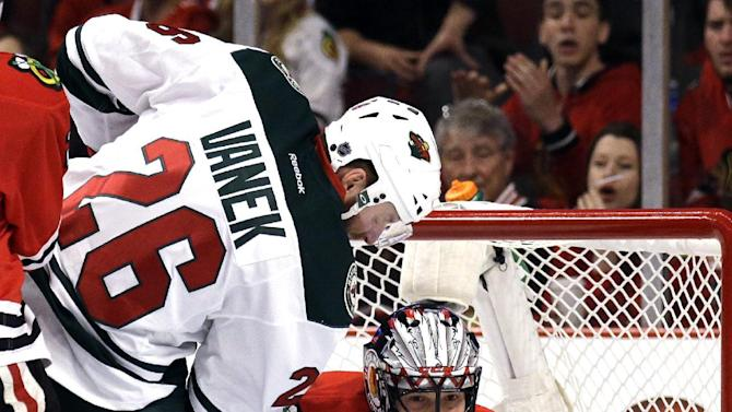 Chicago Blackhawks goalie Corey Crawford, right, blocks ascot by Minnesota Wild left wing Thomas Vanek (26) during the first period  of Game 2 in the second round of the NHL Stanley Cup hockey playoffs in Chicago, Sunday, May 3, 2015. (AP Photo/Nam Y. Huh)
