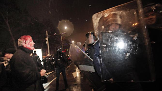 A wounded protester speaks to riot  policemen during a protest against high electricity prices in Sofia, on late Tuesday, Feb. 19, 2013.  Bulgaria's prime minister announced on Tuesday that the license held by a Czech company for power distribution in parts of the Balkan country will be revoked following protests against high electricity prices. (AP Photo/Valentina Petrova)