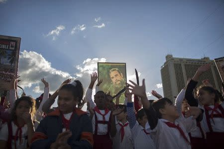 A student holds up a photograph of Cuba's former President Fidel Castro at the memorial of Jose Marti on Revolution Square in Havana