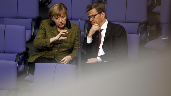 FILE - The Jan. 17, 2013 file photo shows German Chancellor Angela Merkel, left, of the Christian Democratic party and German Foreign Minister Guido Westerwelle, right, of the Liberal Democratic Party FDP talk during a meeting of the German federal parliament, Bundestag,  in Berlin. A defeat for Chancellor Angela Merkel's coalition in a high-profile state election is a blow to the German leader as she seeks a third term later this year — but it's far from clear whether the opposition will be strong enough to oust the popular conservative.  (AP Photo/Michael Sohn)