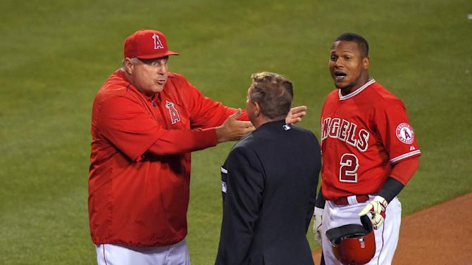 Los Angeles Angels manager Mike Scioscia, left, argues a call with home plate umpire Greg Gibson after Erick Aybar, right, bunted and grounded out to the catcher during the sixth inning of a baseball game against the Seattle Mariners, Tuesday, May 5, 2015, in Anaheim, Calif. (AP Photo/Mark J. Terrill)