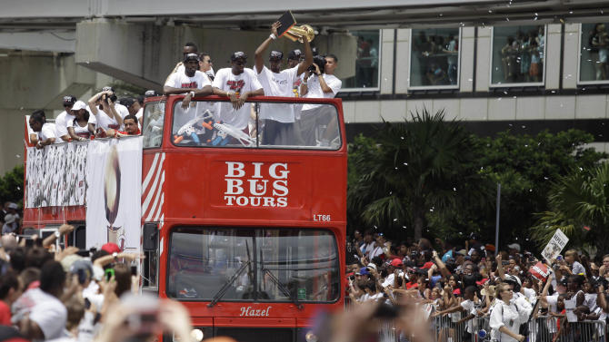 NBA champion Miami Heat's Chris Bosh, right, holds the NBA championship trophy during a parade honoring the team in Miami, Monday, June 24, 2013. (AP Photo/Javier Galeano)