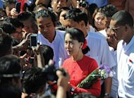 Myanmar democracy icon Aung San Suu Kyi speaks to supporters as she leaves the D. Wave Journal office in Yangon on December 30, 2012. Suu Kyi on Sunday said she would not step in to help end worsening conflict between the army and ethnic Kachin rebels without government approval