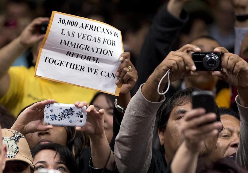 A person in the crowd holds up a sign as President Barack Obama shakes hands after speaking about immigration at Del Sol High School, Tuesday, Jan. 29, 2013, in Las Vegas. (AP Photo/Carolyn Kaster)