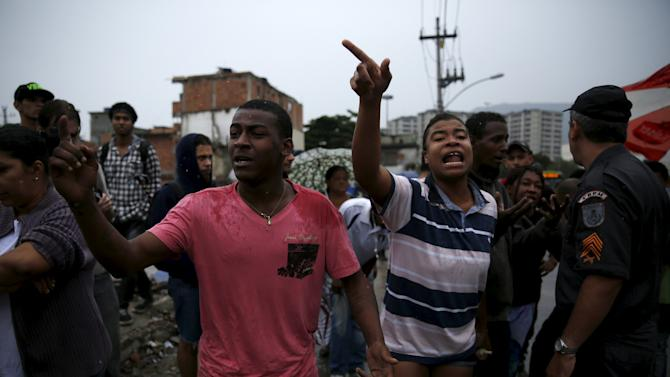 Residents of the Metro Mangueira slum react during an eviction in Rio de Janeiro