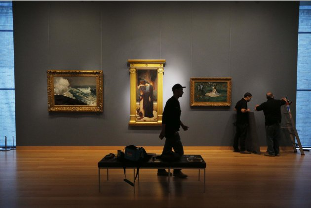 Workers install three paintings on loan from New York's Metropolitan Museum of Art at the Museum of Fine Arts in Boston