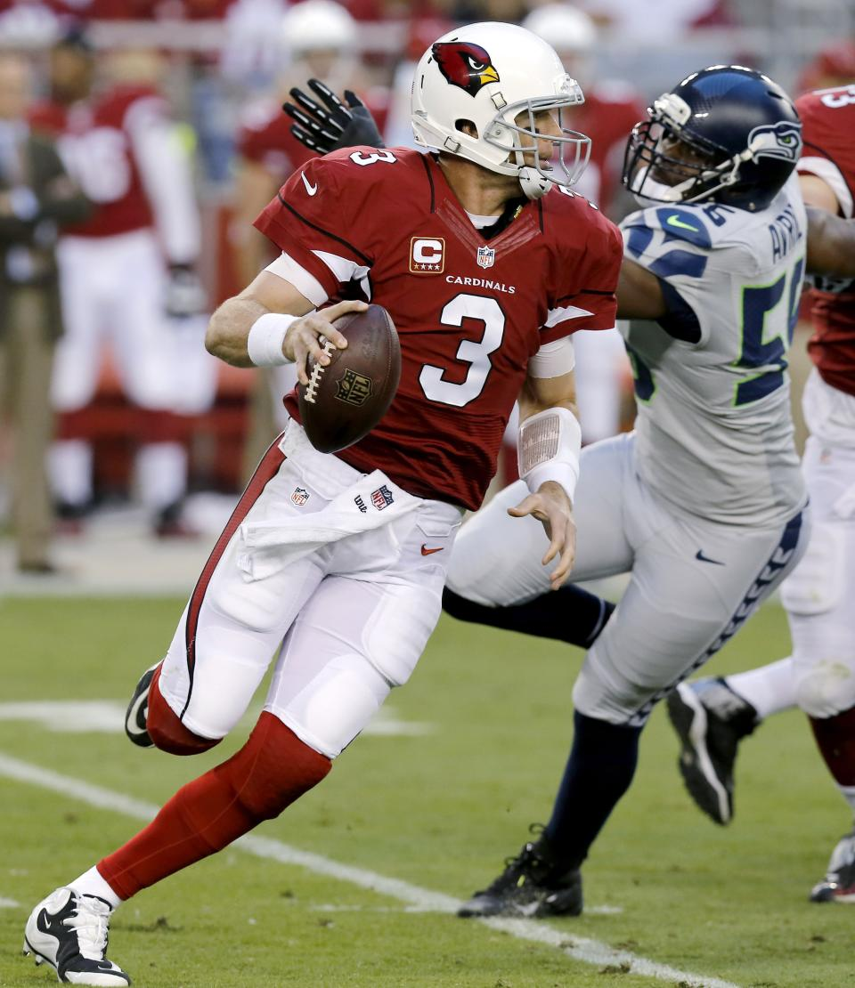 Arizona Cardinals quarterback Carson Palmer (3) scrambles under pressure from Seattle Seahawks defensive end Cliff Avril (56) during the first half of an NFL football game, Thursday, Oct. 17, 2013, in Glendale, Ariz. (AP Photo/Ross D. Franklin)