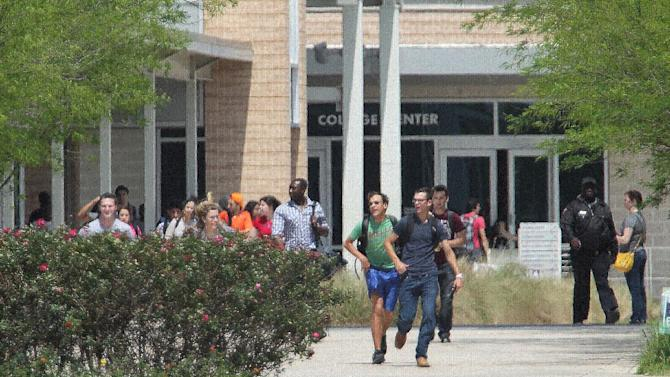 Students run from the Lone Star College's Cypress-Fairbanks campus Tuesday, April 9, 2013, in Cypress, Texas.At least 14 people were hurt in a stabbing at the campus Tuesday.  (AP Photo/Houston Chronicle, James Nielsen)