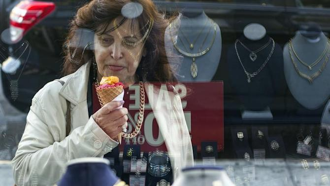 Woman eats ice cream as she looks at the display in the window of a Gold Standard jewellery store in New York