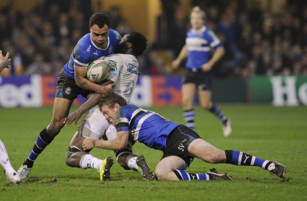 Bath's Olly Woodburn, left, and Sam Vesty, right, combine to tackle Montpellier's Fulgence Ouedraogo, centre, during their Heineken Cup pool 3 rugby match at the Recreation ground, Bath, England, Sund