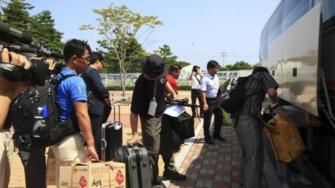 South Korean and Korean-Chinese workers carry their belongings on their arrival at the inter-Korean immigration office in Goseong, South Korea, Tuesday, Aug. 23, 2011 after they returned from the North Korea's Diamond Mountain resort. North Korea has expelled all remaining South Korean workers from the stalled joint tourism resort in the North. (AP Photo/Yonhap, Lee Jong-gun)  KOREA OUT