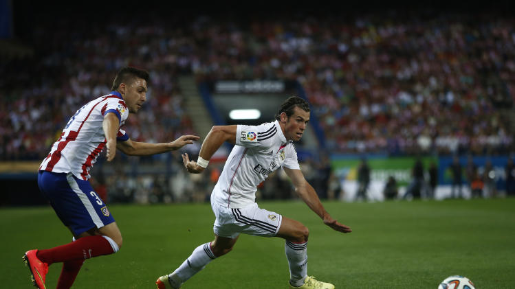 Real's Gareth Bale from Great Britain, centre, in action with Atletico's Atletico's Guilherme Siqueira, left, during a Spanish Supercup second leg soccer match between Real Madrid and Atletico Madrid at Vicente Calderon stadium in Madrid, Spain, Friday, Aug. 22, 2014. (AP Photo/Andres Kudacki)
