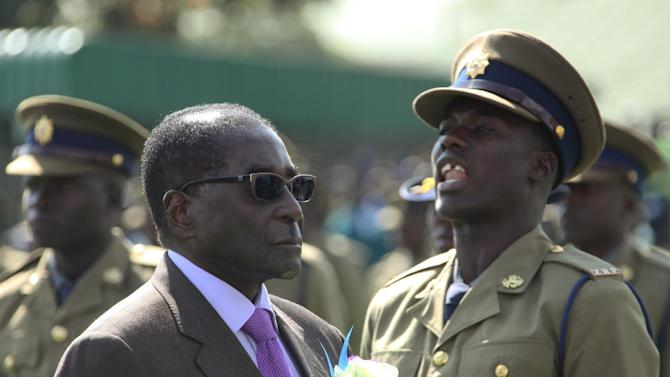 """CORRECTS REFERENCE TO THE DATE OF THE ELECTIONS Police officers are on parade as President Robert Mugabe inspects the guard of honour, at a police pass-out parade in Harare, Thursday, June, 13, 2013. Zimbabwe's prime minister says has received a letter from the President Robert Mugabe saying elections will go ahead on July 31. The communication is the latest development in a standoff between the two leaders over when to hold the long-awaited vote. Prime Minister Morgan Tsvangirai said Thursday that Mugabe should have shown """"mere courtesy"""" by consulting him on the issue. Mugabe was forced by regional leaders to form a coalition government with former opposition leader Tsvangirai after violent and disputed elections in 2008. The longtime president he is abiding by a court ruling calling for the vote to go ahead. (AP Photo/Tsvangirayi Mukwazhi)"""