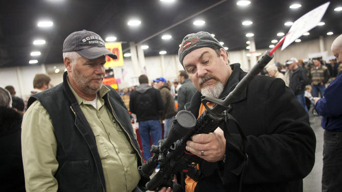 Gun owners discuss a potential sale of an AR-15, one of the most popular and controversial weapons, during the 2013 Rocky Mountain Gun Show at the South Towne Expo Center in Sandy, Utah Saturday, Jan. 5, 2013. In spite of the recent school shooting in Newtown, Conn., gun enthusiasts packed in by the hundreds to purchase weapons and ammunition. The gunman in the Sandy Hook Elementary School shooting in December used an AR-15 to kill 20 first-graders and six educators in the school before killing himself as police closed in. (AP Photo/The Deseret News, Ben Brewer)