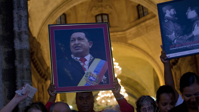 A man holding a framed image of Venezuela's President Hugo Chavez and other parishioner file out of the Cathedral after attending a Mass to pray for the recovery of Chavez, in Havana, Cuba, Saturday, Jan. 12, 2013. The 58-year-old president is fighting a severe respiratory infection a month after he underwent cancer surgery in Havana, his government says. (AP Photo/Ramon Espinosa)