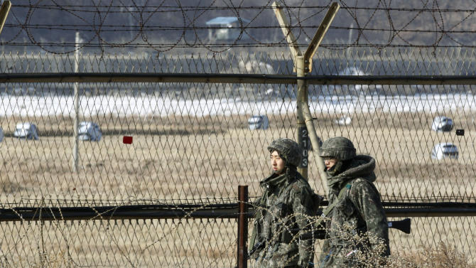 """South Korean army soldiers patrol along a barbed-wire fence in Paju, South Korea, near the demilitarized zone (DMZ) of Panmunjom, Sunday, Jan. 27, 2013.   North Korean leader Kim Jong Un convened top security and foreign affairs officials and ordered them to take """"substantial and high-profile important state measures,"""" state media said Sunday, indicating that he plans to push forward with a threat to explode a nuclear device in defiance of the United Nations. (AP Photo/Ahn Young-joon)"""