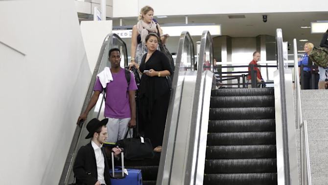 Shalom Sharley, bottom left, of New York, checks his watch while riding on an escalator before checking in for his United Airlines flight to Tel Aviv at Newark Liberty International Airport, Thursday, July 24, 2014, in Newark, N.J. United Airlines will be the first U.S. carrier to resume flights to Israel after a two-day hiatus caused by combat in the Gaza Strip. The Chicago-based airline says it will resume service to Ben Gurion Airport in Tel Aviv with a 4:45 p.m. eastern flight from Newark Liberty International Airport in New Jersey. A second United flight will leave Newark at 10:50 p.m. eastern. The decision comes hours after the Federal Aviation Administration lifted its ban on U.S. flights in and out of Israel, which the agency had imposed out of concern for the risk of planes being hit by Hamas rockets. (AP Photo)