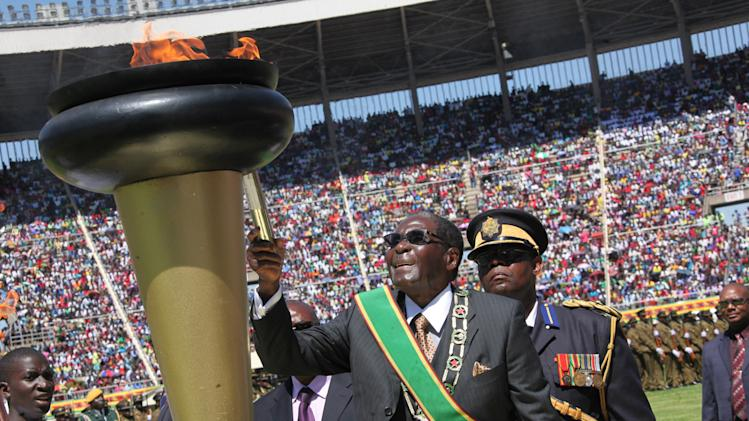 Zimbabwe's President Robert Mugabe lights the independence flame during Zimbabwe's 33rd independence celebrations in Harare, Thursday, April, 18, 2013. (AP Photo/Tsvangirayi Mukwazhi)