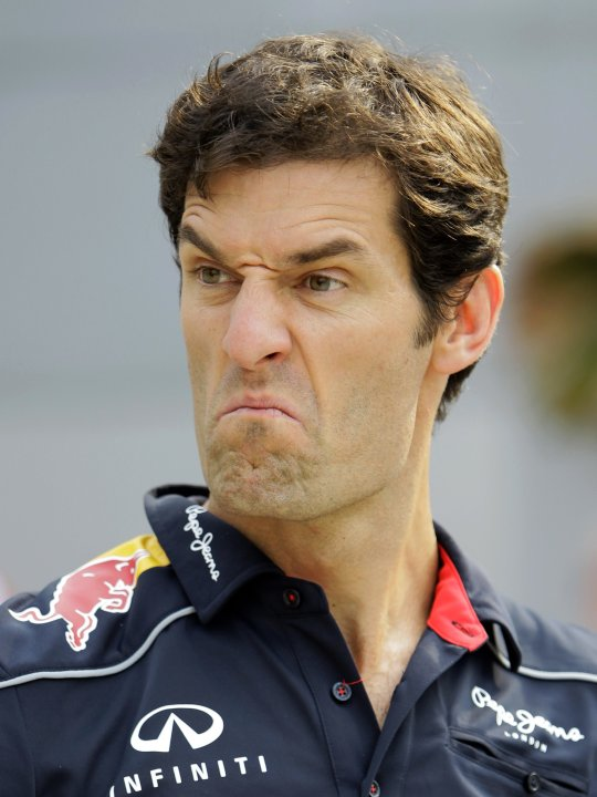 Red Bull Formula One driver Mark Webber of Australia reacts to a joke by his team members at the paddock of Sepang International Circuit