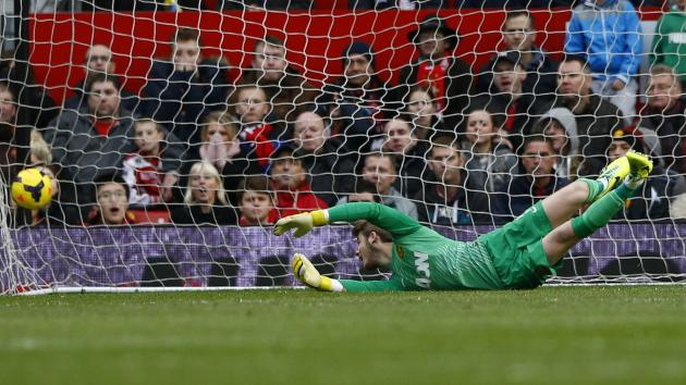 Manchester United's goalkeeper David de Gea dives for the ball as Newcastle United's Yohan Cabaye scores a goal during their English Premier League soccer match at Old Trafford in Manchester