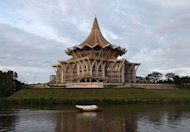 A boat passes by the Sarawak State Legislative Assembly in Kuching, the capital city of Malaysia's Sarawak state, on February 7, 2013. A state minister said Sarawak gov't will not push ahead with building 12 controversial dams amid anger among local tribes and environmentalists over the plans