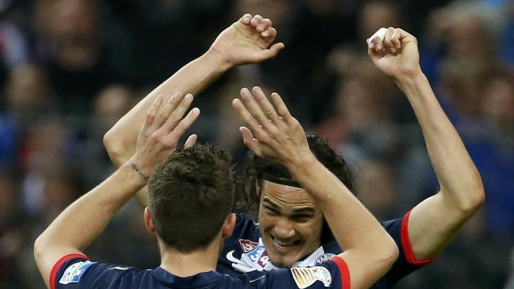 Paris St Germain's Cavani celebrates with team mate Cabaye after defeating Olympique Lyon in the French League Cup final soccer match at the Stade de France stadium in Saint-Denis