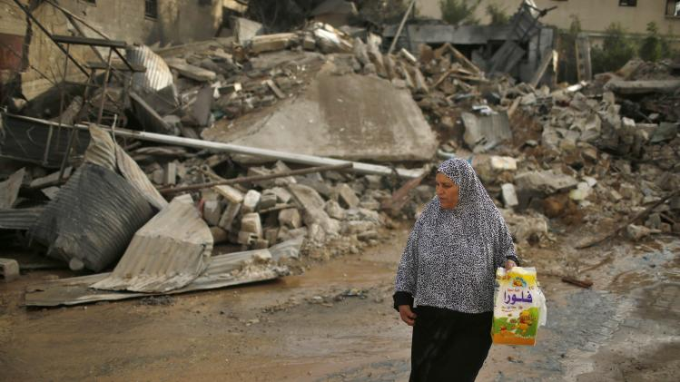 Palestinian woman walks past a house which police said was destroyed in an Israeli air strike in Gaza City