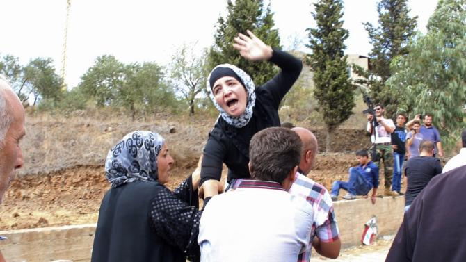 The mother of a Lebanese soldier killed in a roadside bomb is helped by relatives as she mourns during his funeral in Aidmon