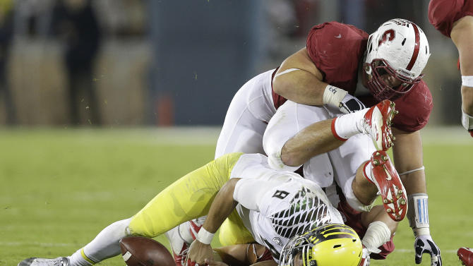 Oregon quarterback Marcus Mariota (8) fumbles as he is tackled by Stanford defensive tackle David Parry, top, and linebacker A.J. Tarpley during the third quarter of an NCAA college football game in Stanford, Calif., Thursday, Nov. 7, 2013. Stanford recovered the fumble. (AP Photo/Marcio Jose Sanchez)