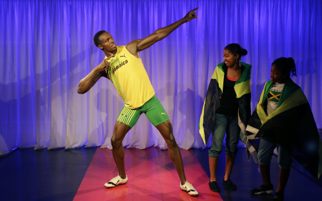 Fans look at the new wax model of Jamaican sprinter Usain Bolt, at a photocall for its launch at the Madame Tussauds wax museum, ahead of the 2012 Summer Olympics, Monday, July 23, 2012, in London. (AP Photo/Ben Curtis)