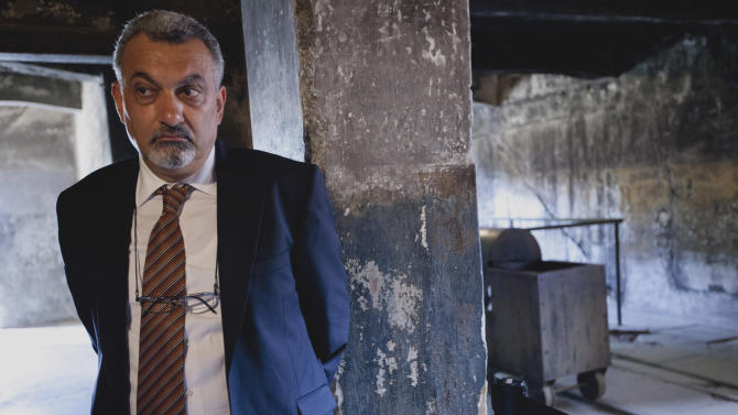 Ziad al-Bandak, adviser to Palestinian President Mahmoud Abbas on Christian affairs,  visits the Birkenau part of the former German Nazi death camp of Auschwitz-Birkenau as he pays respect to some 1.5 million of the World War II camp victims, mostly Jews, in Oswiecim, Poland on Friday, July 27, 2012. Al-Bandak laid flowers at the Death Wall where Polish resistance movement members were executed and lit a candle at the monument to the camp's victims, who came from many nations. (AP Photo/Jarek Praszkiewicz)