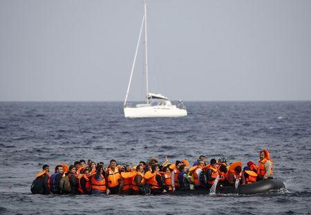 Syrian refugees empty water from their raft as they approach the Greek island of Lesbos