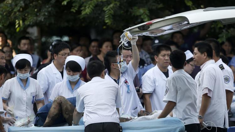 Medical personnel transport a victim of a factory explosion at a hospital in Kunshan