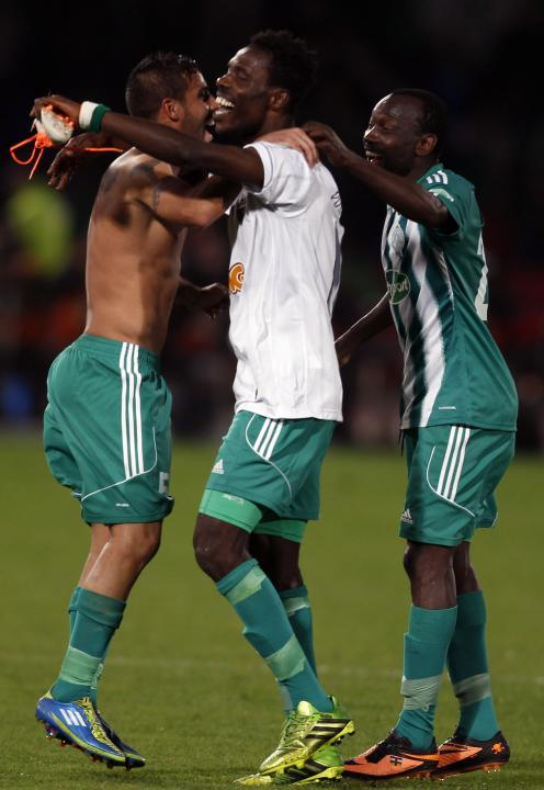 Raja Casablanca players dance with jersey and the shoes of Atletico Mineiro's Ronaldinho after their FIFA Club World Cup semi-final match at Marrakech stadium
