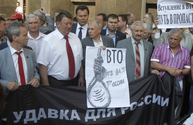 "Members of Communist faction of parliament hold banners that read: ""WTO is a Noose for Russia"", left, and ""Joining WTO is the way to the Precipice"", at right, as they picket outside the parliament headquarters in Moscow, Russia, Tuesday, July 10, 2012. Russia's parliament is due to ratify an agreement for Russia to join the World Trade Organization in a move that will push Moscow to open up its economy. (AP Photo/Misha Japaridze)"