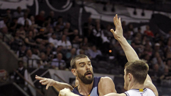 Memphis Grizzlies' Marc Gasol, center, looks to pass against San Antonio Spurs' Aron Baynes, right, and Manu Ginobili, left, during the first quarter of an NBA basketball game, Sunday, March 29, 2015, in San Antonio. (AP Photo/Michael Thomas)