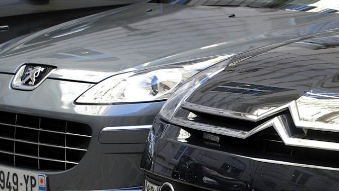 In this Sept. 7, 2012 file photo, a Peugeot, left, and Citroen cars are parked in Paris. PSA Peugeot Citroen posted Wednesday, Feb,13, 2013 a record Euro 5 billion ($6.7 billion) loss last year after Europe's cratering car market forced France's largest automaker to book a Euro 3 billion financial charge. As well as falling demand, which led to a 12.4 percent slump in new vehicle sales to Euro 27.8 billion, the Paris-based company had to contend with the rising cost of steel and other materials. (AP Photo/Jacques Brinon, File)