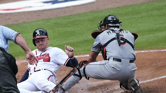 Atlanta Braves' Freddie Freeman (5) beats the tag from Miami Marlins catcher Jeff Mathis (6) to score on a Hector Olivera base hit in the third inning of a baseball game Wednesday, Sept. 2, 2015, in Atlanta. (AP Photo/John Bazemore)