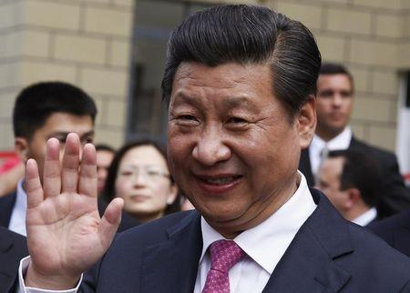 China's President Xi waves during a visit to a housing development in Caracas