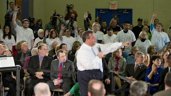 """FILE - In this March 20, 2014 file photo, Demonstrators stand with the word """"Bridgegate"""" spelled out on their shirts as New Jersey Gov. Chris Christie selects a person to ask him a question at a town hall-style meeting at St. Magdalen de Pazzi parish center in Flemington, N.J. Critics of Christie are making their voices heard like never before. Opponents are showing up at the Republican governor's every public appearance, waving signs and shouting criticisms on a range of topics including a plot by his aides to tie up traffic near the world's busiest bridge. (AP Photo/Matt Rourke)"""