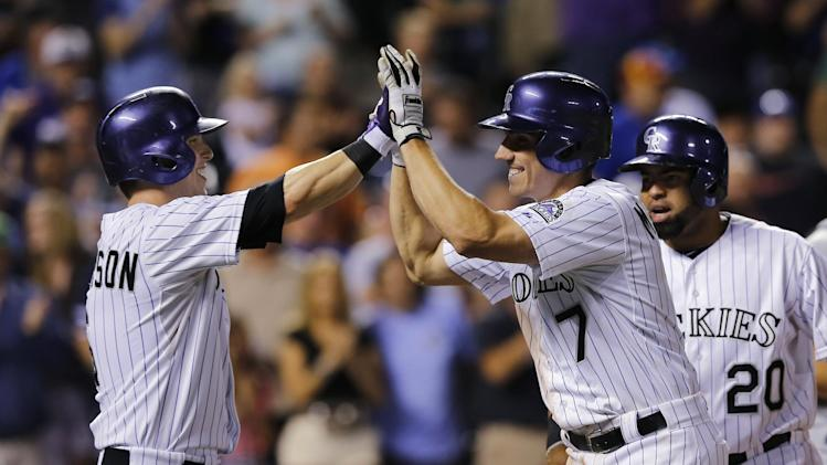 Colorado Rockies' Matt McBride (7) is congratulated at the plate by teammates Corey Dickerson, left, and Wilin Rosario after hitting a grand slam off Kansas City Royals starting pitcher Danny Duffy during the sixth inning of a baseball game Wednesday, Aug. 20, 2014, in Denver. (AP Photo/Jack Dempsey)