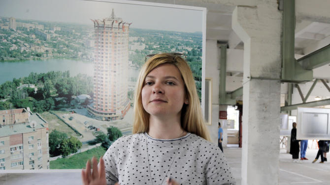 In this May 13, 2015, photo, Alesya Bolot gestures during an interview in Kiev, Ukraine. Bolot worked for a contemporary arts foundation that converted an abandoned factory into a mecca for young and bright people with daring ideas. She arrived in the capital Kiev a year ago with only a backpack, not planning a long-term stay. But she decided to remain after she was told she was on the wanted list of the self-styled Donetsk People's Republic, for alleged subversive activity. More than 2.2 million people have fled their homes in eastern Ukraine since the war between government forces and Russia-backed separatists began in April last year, according to the United Nations,  (AP Photo/Efrem Lukatsky)