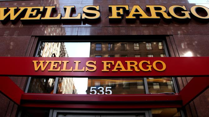 In this May 6, 2012, photo, a Wells Fargo sign is displayed at a branch in New York. Wells Fargo is reporting higher earnings for the second quarter thanks to a pickup in lending and a decline in the amount of bad loans, according to reports Friday, July 13, 2012. (AP Photo/CX Matiash)