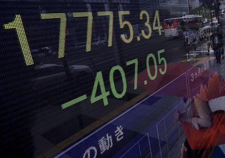 A pedestrian holding her umbrella is reflected on an electronic board showing the Japan's Nikkei average outside a brokerage in Tokyo