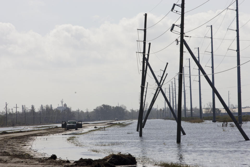 A truck is stranded from receding flood waters from Hurricane Isaac along Louisiana Hwy 23 near Port Sulphur, La., in Plaquemines Parish, Monday, Sept. 3, 2012. (AP Photo/Matthew Hinton)