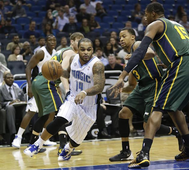 Orlando Magic's Jameer Nelson (14) drives around Utah Jazz's Trey Burke (3) and Derrick Favors (15) during the first half of an NBA basketball game in Orlando, Fla., Wednesday, Dec. 18, 2013.
