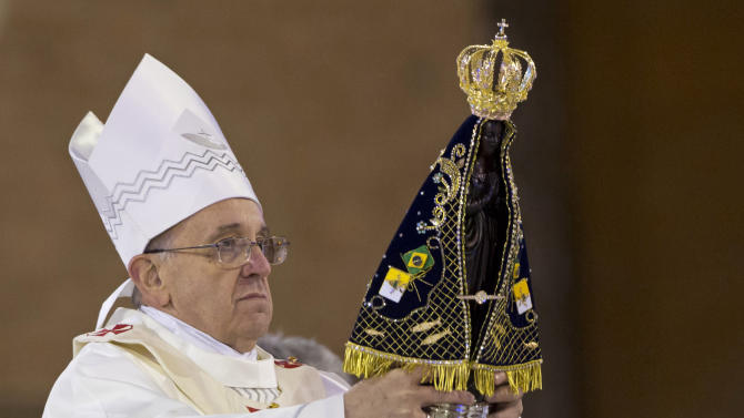 Pope Francis holds up the statue of the Virgin of Aparecida, Brazil's patron saint, during Mass in the Aparecida Basilica in Aparecida, Brazil, Wednesday, July 24, 2013. Reverence for the figure of the Virgin Mary runs particularly deep in Latin America. The Vatican says that Pope Francis personally insisted that a trip to the Aparecida Basilica be added to his Brazilian visit agenda. (AP Photo/Felipe Dana)