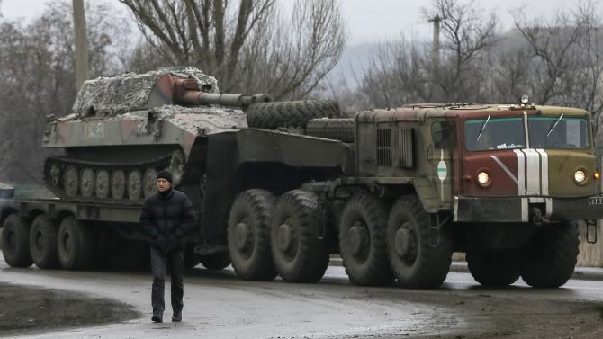 A local resident walks as a military truck from the Ukrainian armed forces transports a self-propelled howitzer on the road near Artemivsk