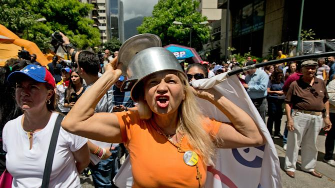 An opposition member wearing a pot on her head shouts slogans against Venezuela's President Nicolas Maduro during a protest in Caracas, Venezuela, Saturday, Feb. 28, 2015. Marchers are taking to the streets of Caracas in dueling protests, with one group calling attention to a crackdown on opponents of the government and another showing support for the embattled socialist administration. (AP Photo/Fernando Llano)